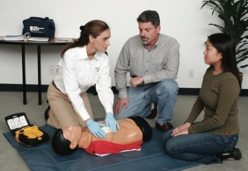 An image of a ZEE Medical staff member giving an AED training to a man and woman couple. All are kneeling on the ground next to a CPR dummy