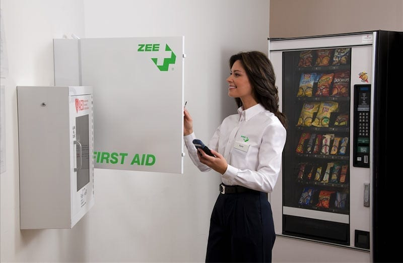 an image of a ZEE Medical worker checking on a ZEE Medical cabinet at a customer's office building