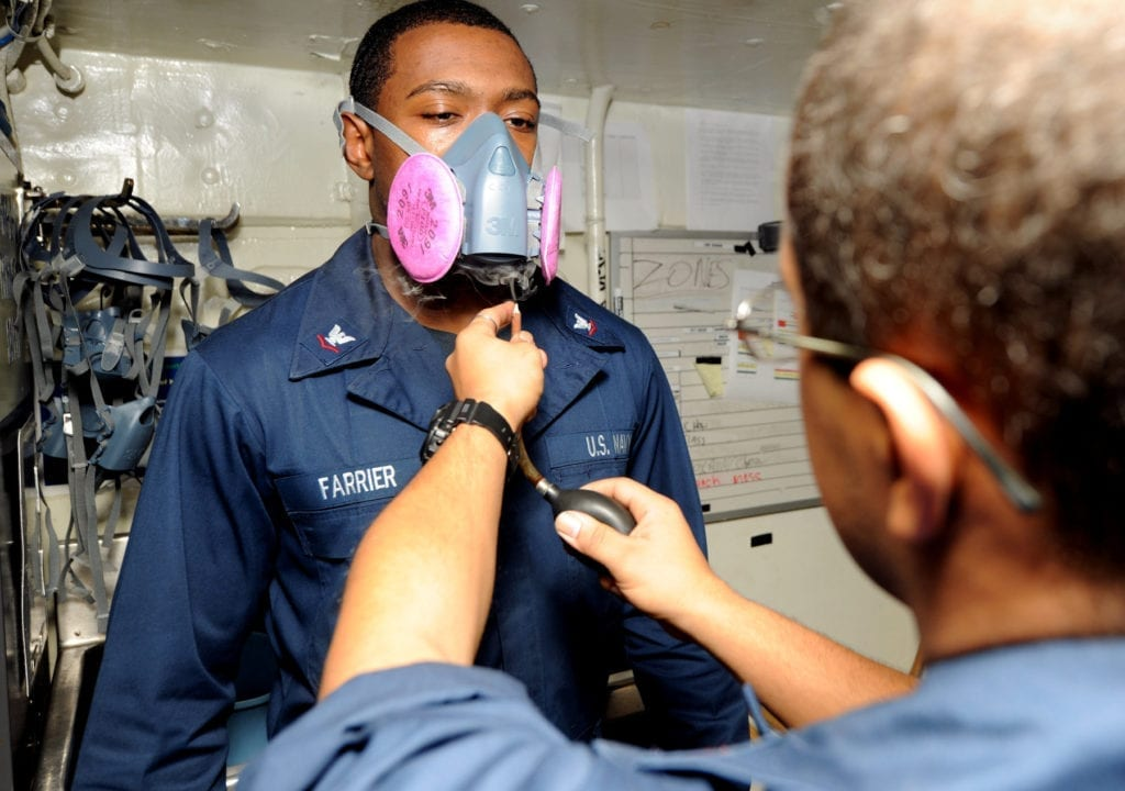 110429-N-7326M-028 ARABIAN GULF (April 29, 2011) Boatswain's Mate 3rd Class Shaka K. Farrier dons a respirator as irritant smoke is released into the air as part of a respirator fit test aboard the aircraft carrier USS Enterprise (CVN 65). Enterprise aand Carrier Air Wing (CVW) 1 are conducting operations in support of Operation New Dawn in the U.S. 5th Fleet area of responsibility. (U.S. Navy photo by Mass Communication Specialist Seaman Daniel J. Meshel/Released)
